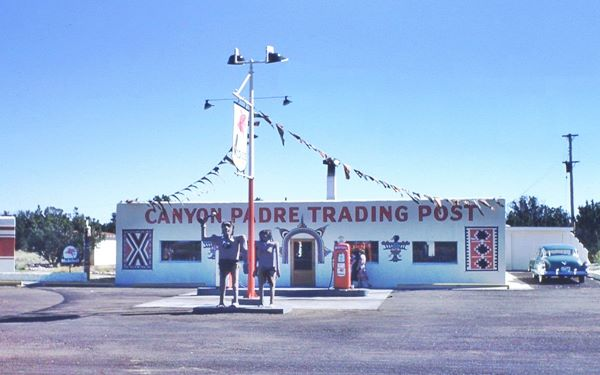 pre-1955 view of the trading post, vintage car, gas pumps