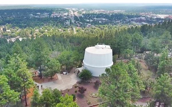 observatory dome on a forested hill surrounded by pine trees