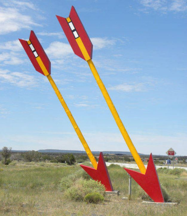 close up of the two giant arrows, painted red and yellow, stuck in the ground