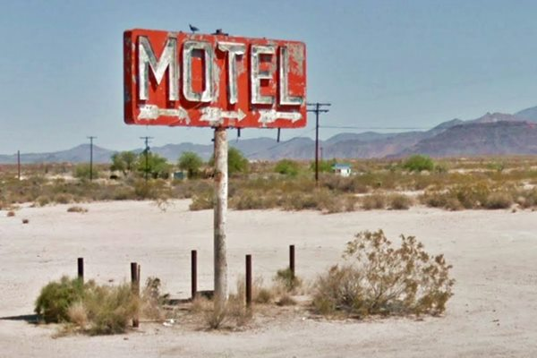 Red rusting and fading motel sign in the desert