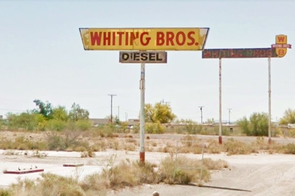 gas station signs, rusting in the desert
