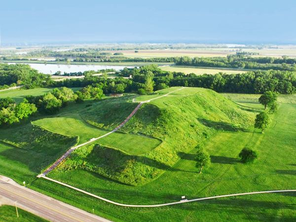 enormous mound covered with grass among trees seen from the air, Route 66 next to it