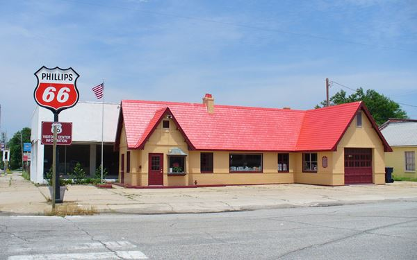 L-shaped cottage style station with red tiled hipped roof with gables and chimney