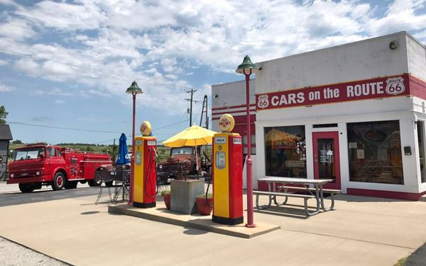gas station in red and white, pumps, and three Cars characters