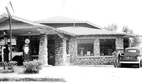 black and white photo of the gas station, with an old truck and gas pumps