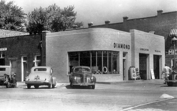 black and white photo with 1940s cars and gas station