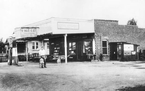 black and white picture of store, gas pumps, man and chiled ca. 1930