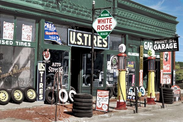 colorized photo of the old garage with gas pumps, tires and enamel signs