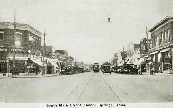 black and white picture ca. 1920 of Military Ave and 11th St. cars, tram and people