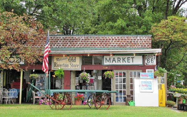 the historic store, green lawn, flag, shop, ice machine and old cart