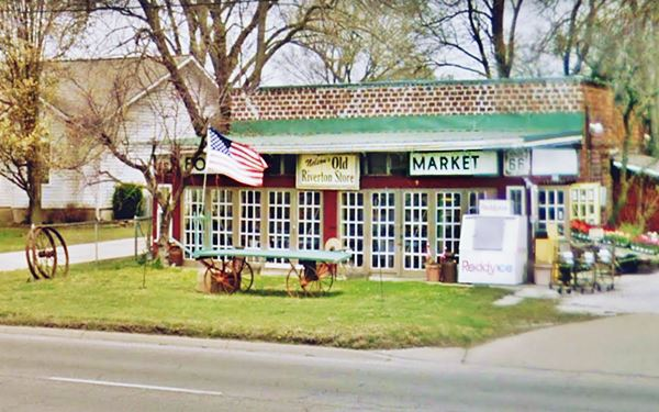 store with lawn in front, an American flag and trees behing