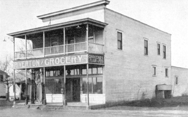 black and white 1930s picture old 2 floor building with gas pumps