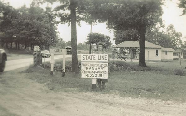 1940s view of trees, US66, homes and a woman by the KS-MO state line sign