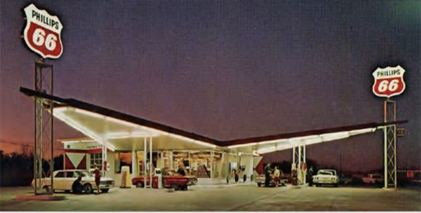 Lit up Phillips Harlequin service station with two wing canopies, at night