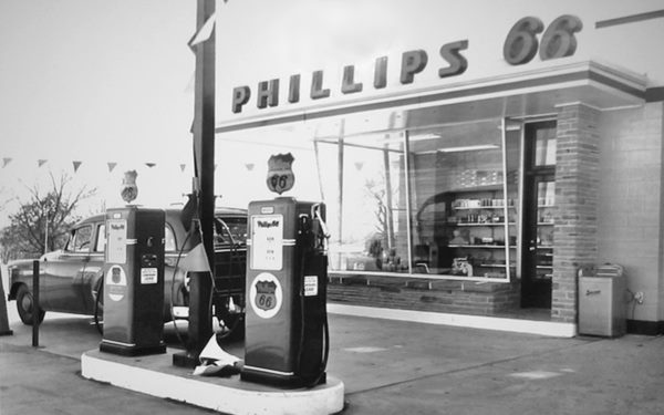 canted glass, rock faced 1950s service station with its pumps and a car