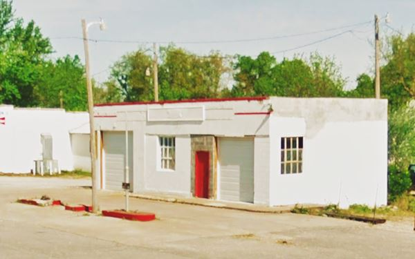 shuttered old gas station, whitewashed walls