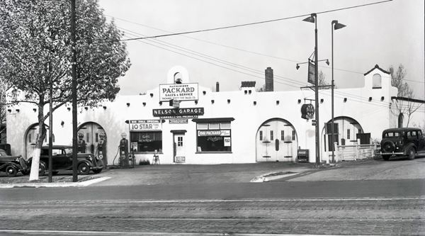 1930s black and white photo of a gas station with cars