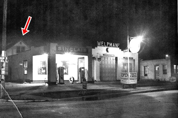 1950s photo with a night view of a Sinclair gas station in black and white