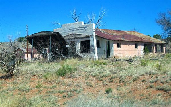 old store on hill with trees, in ruins