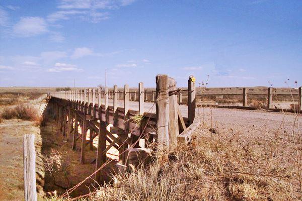 wood bridge crossing dry river