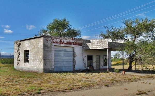 former Texaco gas station with tree growing in the gas pump island