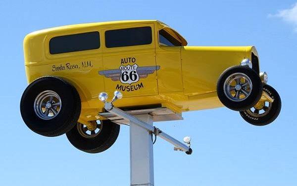 A yellow car atop a pole