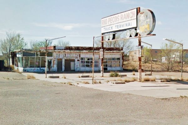 old service station with a large fading neon sign