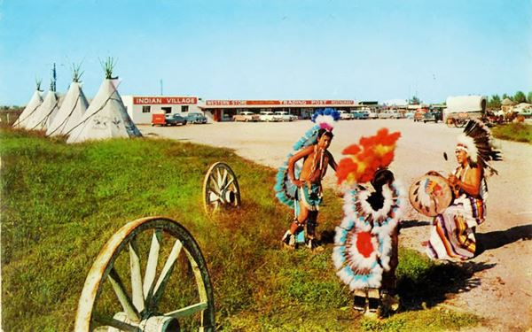 Indians, dancing, teepees, 1950s cars and a trading post in a color postcard ca.1950