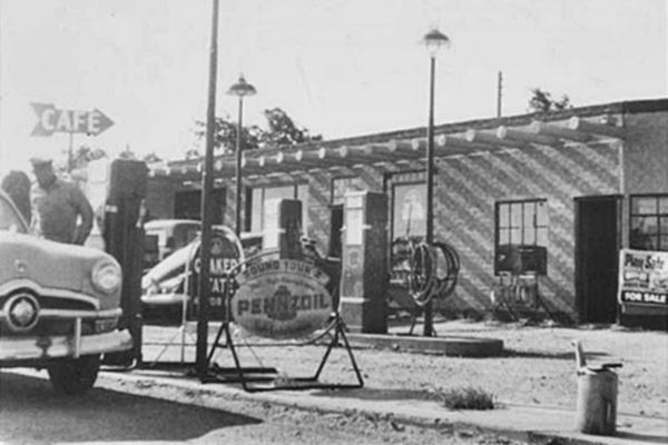 old cars at pump, Phillips 66 and cafe sign, black and white picture circa 1950s