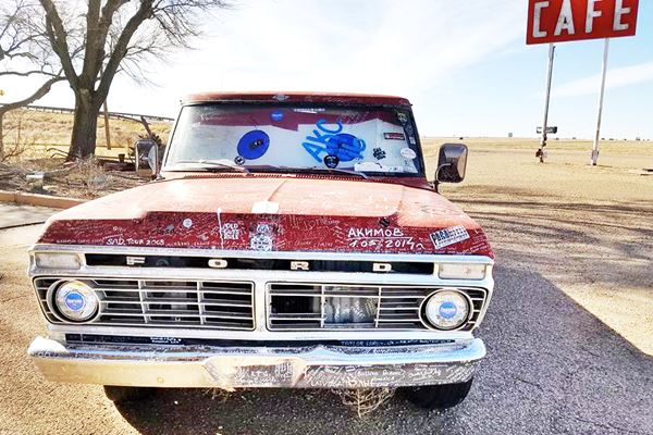 red pick up truck with hundreds of white signatures on it