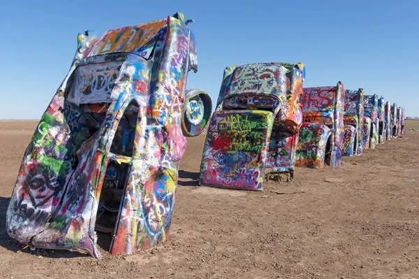 front view of grafitti covered and buried cadillacs