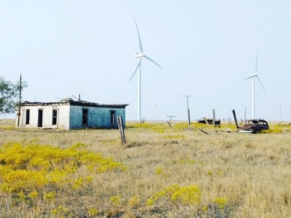 old house, collapsed roof and rusty car in a field wind generators in the background
