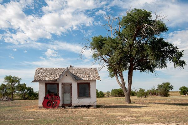 1920s cottage style Phillips 66 in a field by a tree