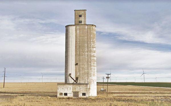 old tall concrete silo and grain elevatorin a field