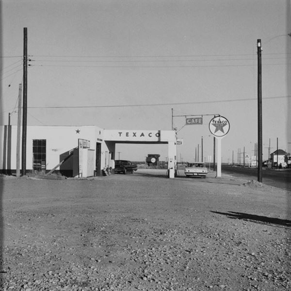 black and white photo of the gas station with a car and US66 to the right