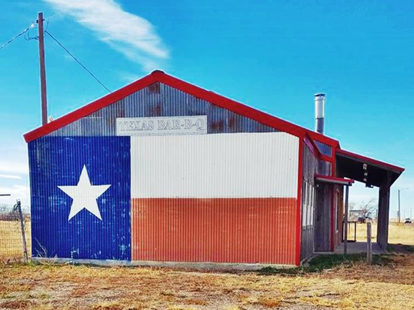 A flag of Texas painted on the wall of a gabled house
